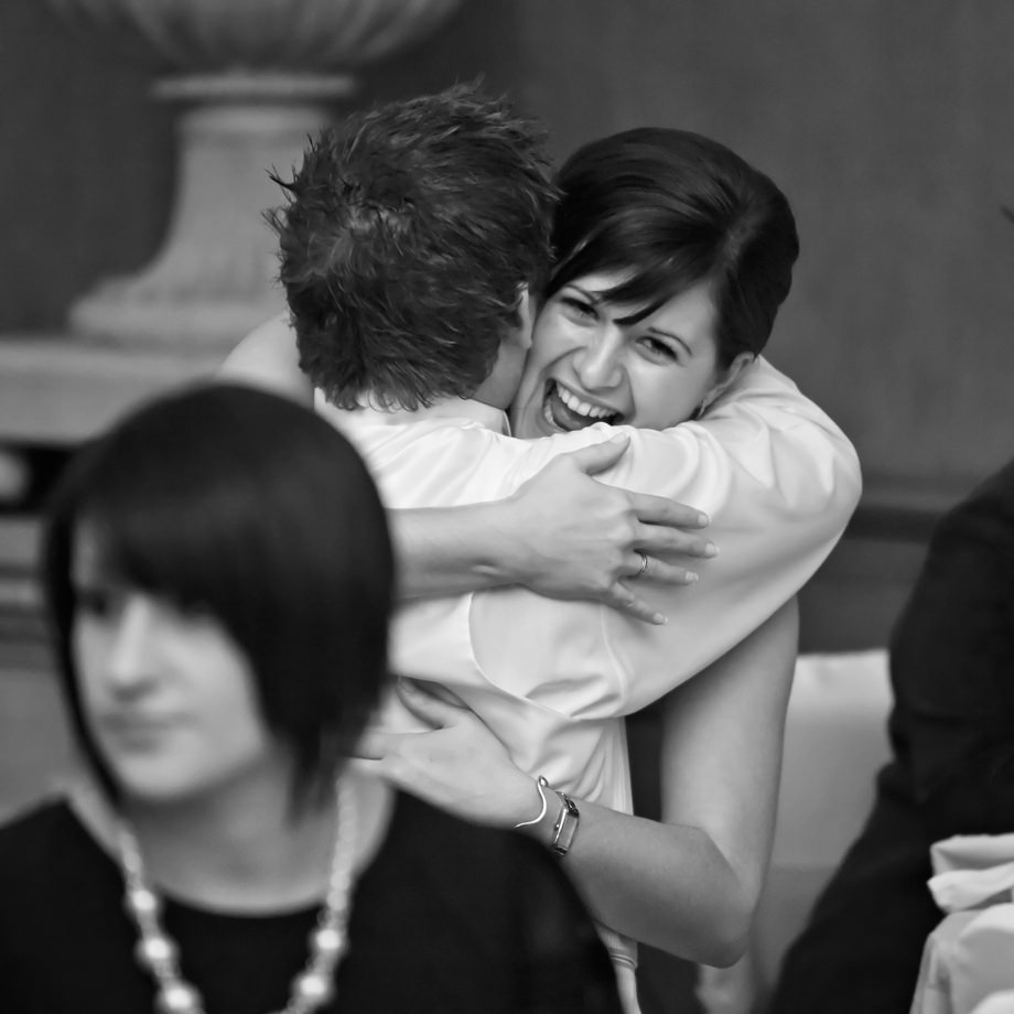 a wedding guest hugs the groom at halswell house in somerset