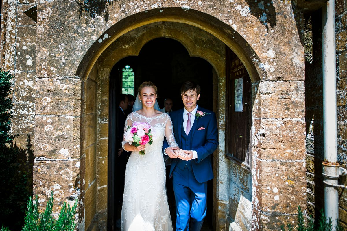 bride and groom leave brympton church