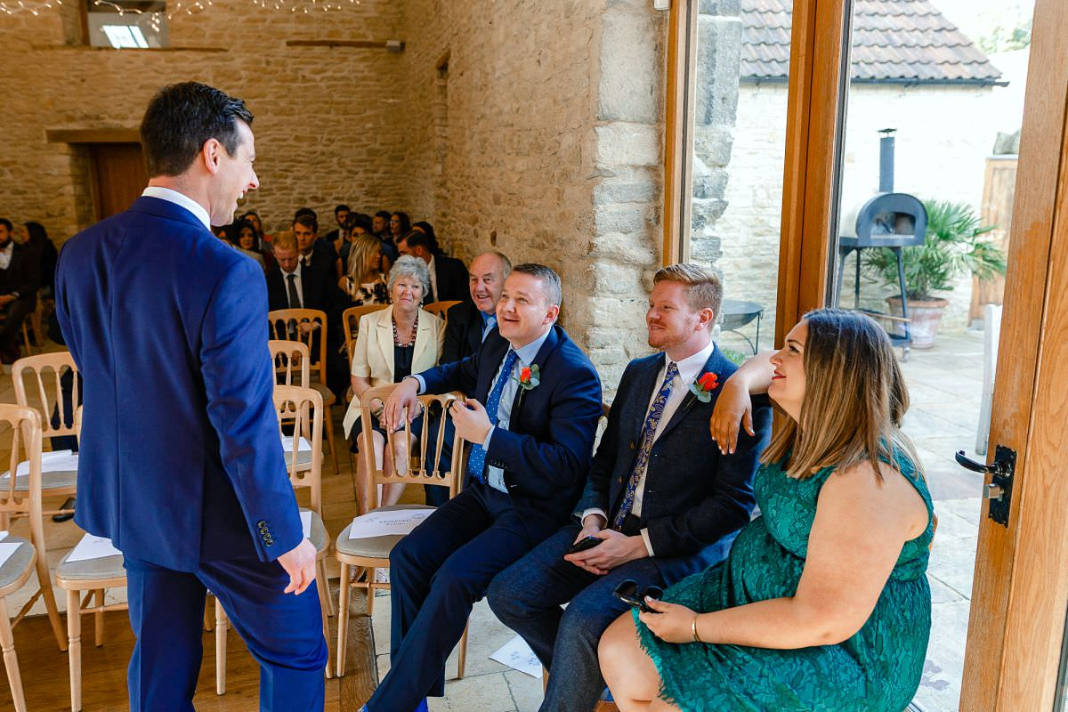 groom talking to guests at kingscote barn